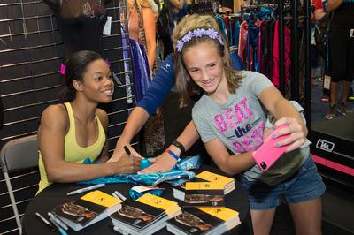 Gabrielle Douglas signs autographs
