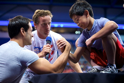 John Macready watches over a arm-wrestling match between a fan and David Durante