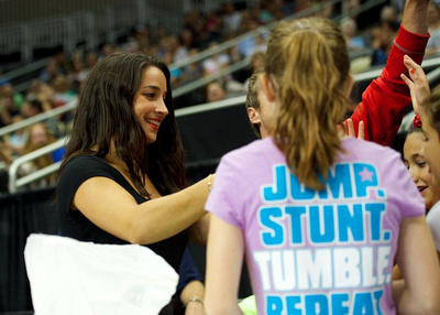 Aly Raisman hands some prizes to some fans