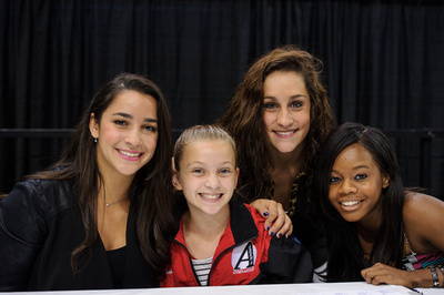 Aly Raisman, Jordyn Wieber and Gabby Douglas pose for a picture with a fan