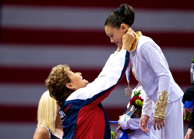 Kyla Ross receives her gold medal from Martha Karolyi